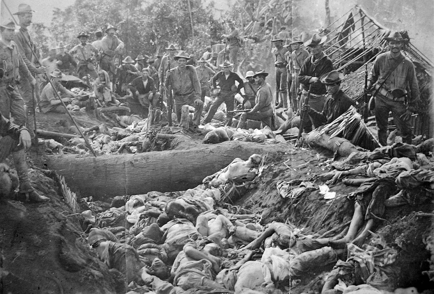 US Soldiers pose with Filipino Moro dead after the First Battle of Bud Dajo, March 7, 1906, Jolo, Philippines.