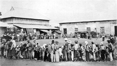 """Original caption:  """"Gov'mt. issuing rice to poor people in Bauan during the concentration."""" Photo was taken in 1901 at Bauan, Batangas Province. The town was garrisoned by Troop K of the 1st US Cavalry Regiment."""