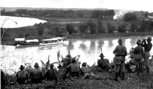 """Original caption: """"Taking of Pasig --- In the distance to the left the city is seen, and in front the puffs of smoke from the insurgents' rifles, while half way down the open field the American line is returning the fire, being reenforced by others who are hurrying from the boat on the other side of the river. In the background are the reserve troops who have been protecting the advance."""""""