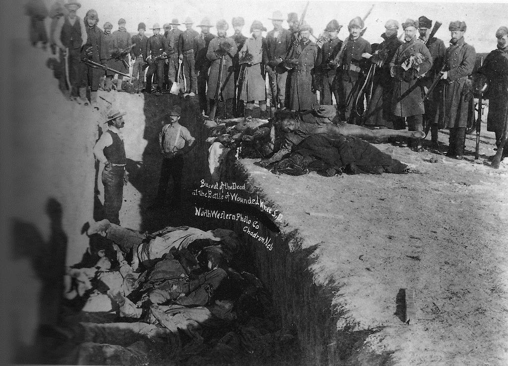 U.S. soldiers pose for a picture near a mass grave of dead Lakotas following the Wounded Knee Massacre of December 29, 1890